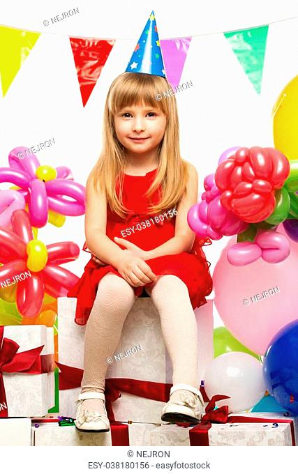 Little girl in red dress sitting on gift boxes
