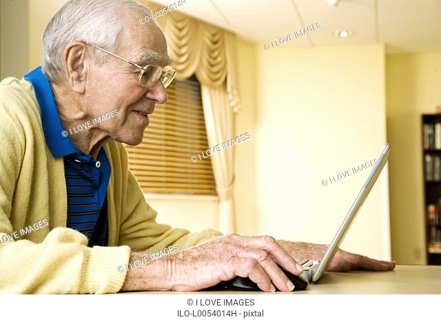 An elderly man using a laptop