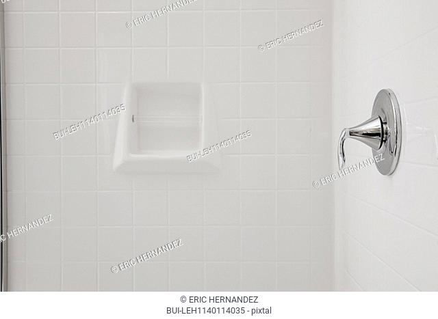 Close-up of a soap dish and tap on tiled bathroom wall at home