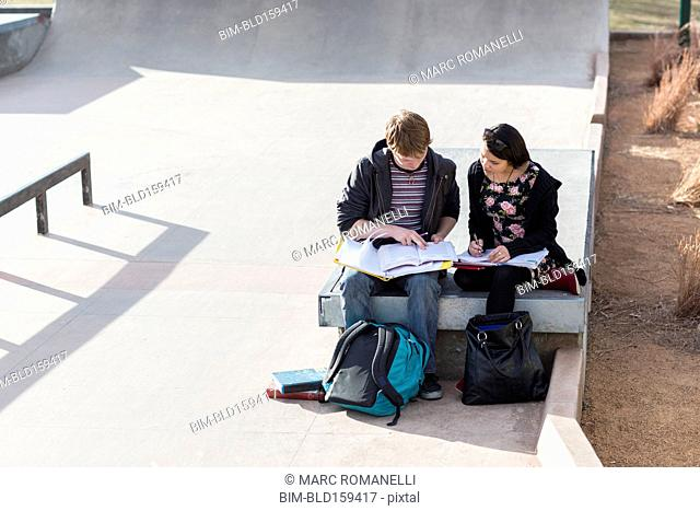 Teenage students studying in skateboard park