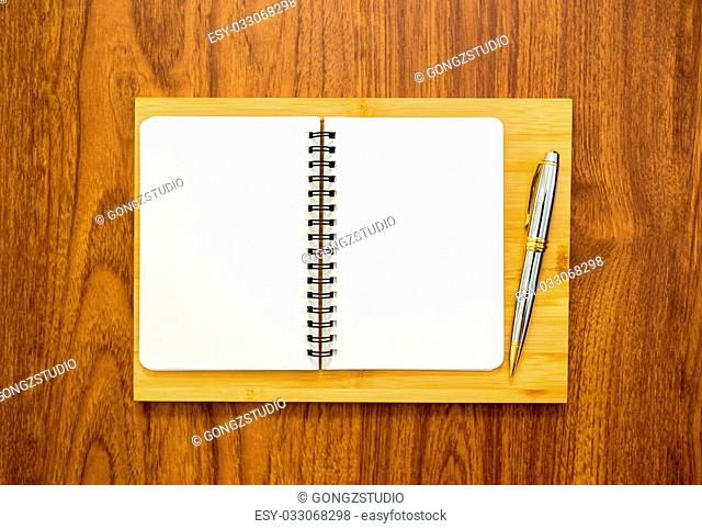 Blank notebook with a pen on wood background