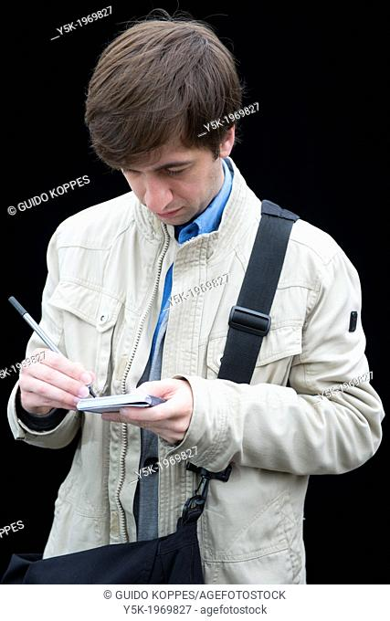 Tilburg, Netherlands. Portrait of a young intellectual male, writing down notes on his vintage notepad during a portrait session on the weekly market