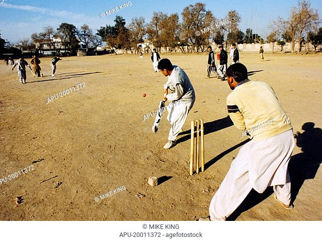 Men playing cricket on dirt field