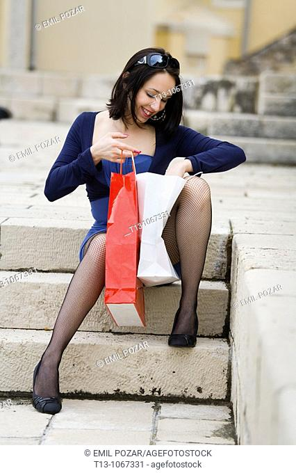 Attractive young woman is looking into her shopping bags