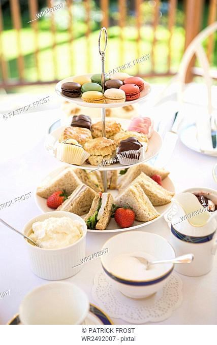 Cake stand with sandwiches, cookies and macaroons