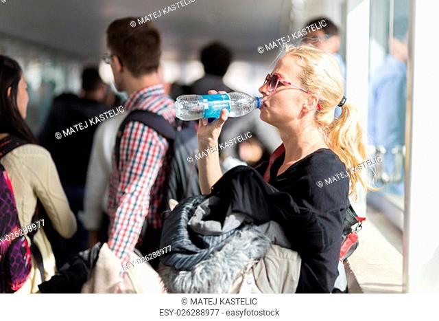 Young blond caucsian woman drinking water while waiting in queue to board plane
