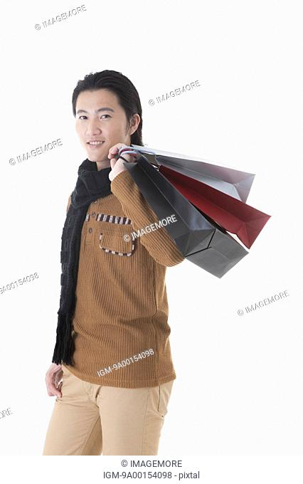 Mid adult man carrying shopping bags on shoulder