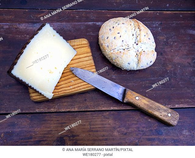 A wedge of cheese on a wooden board with an antique knife and rustic spanish bread