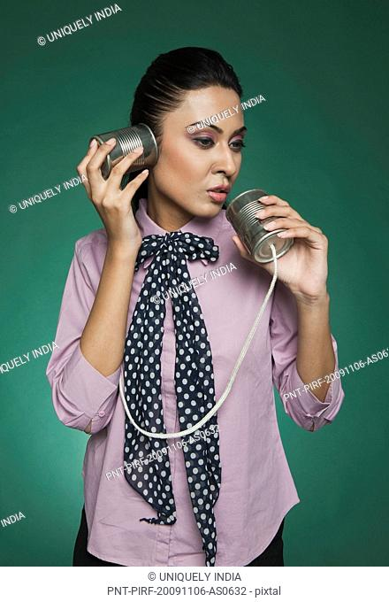 Businesswoman using a tin can phone