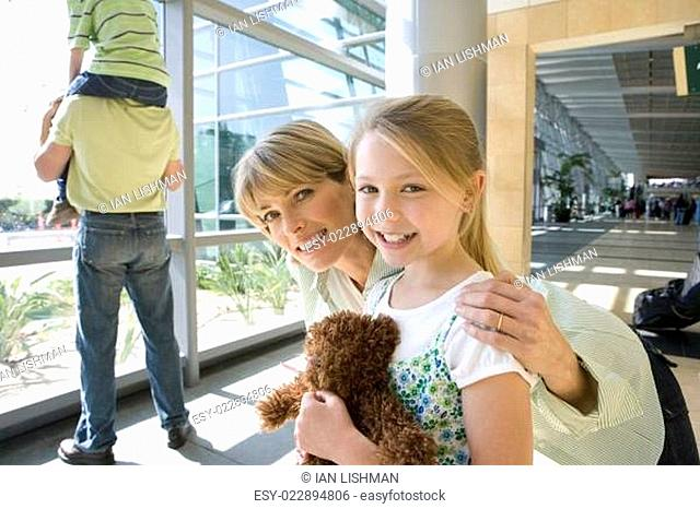 Boy (8-10) sitting on father&#xe2 &#x20ac &#x2122 s shoulders beside window in airport, focus on mother and daughter (7-9) in foreground, smiling, portrait