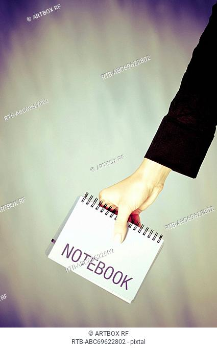 Close-up of a person's hand holding a spiral notebook