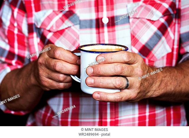 Specialist coffee shop. A man holding a cup of coffee