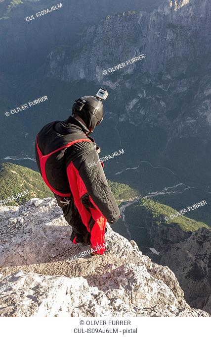 BASE jumper on mountain edge, Alleghe, Dolomites, Italy