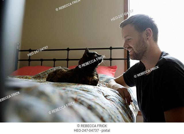 Man and cat face to face in bedroom