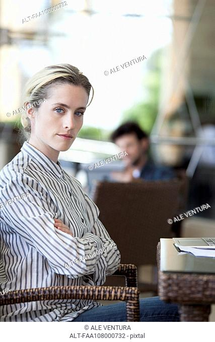 Woman with arms folded and determined look on face, portrait