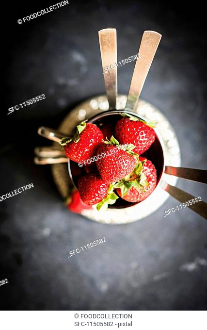 Fresh strawberries in silver bowls
