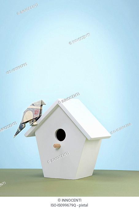 Origami yen banknote imitating bird on bird box