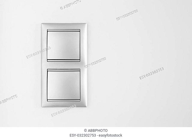 Double metallic light switch over a white wall. Copy space. Horizontal