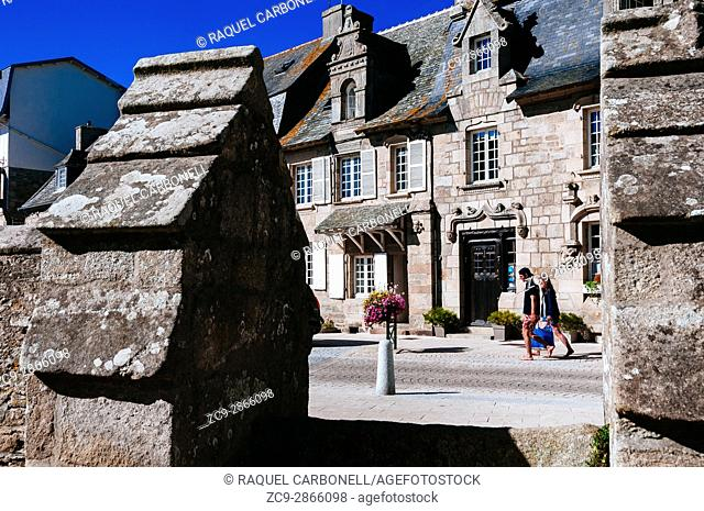 Couple walking on street passing by traditional fifteenth-century stone houses. Morlaix, Brittany, France