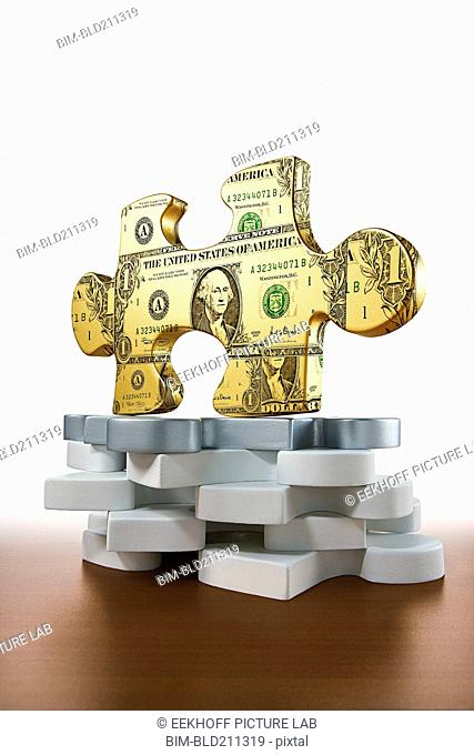 Gold piece of jigsaw puzzle printed with dollars