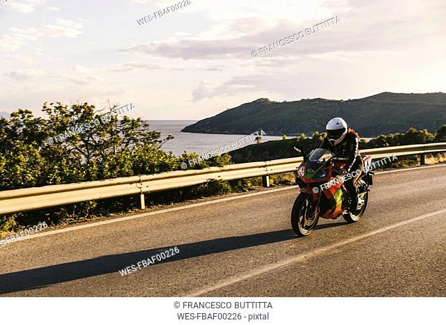 Italy, Elba island, female motorcyclist biking