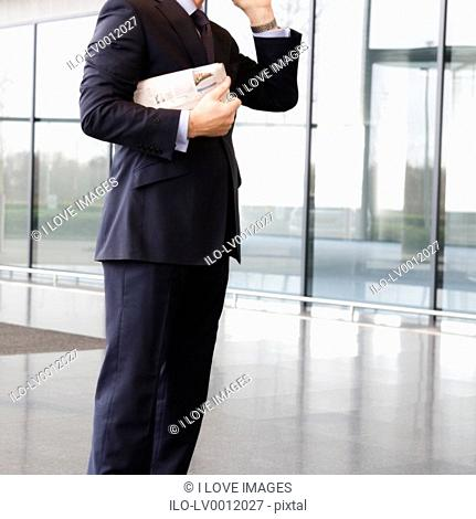 A businessman in a smart suit holding a newspaper