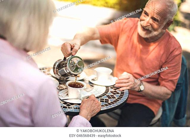 Here you are. Waist up portrait of happy mature male pouring hot drink into cup while having dinner with wife. They are sitting at table and admiring precious...