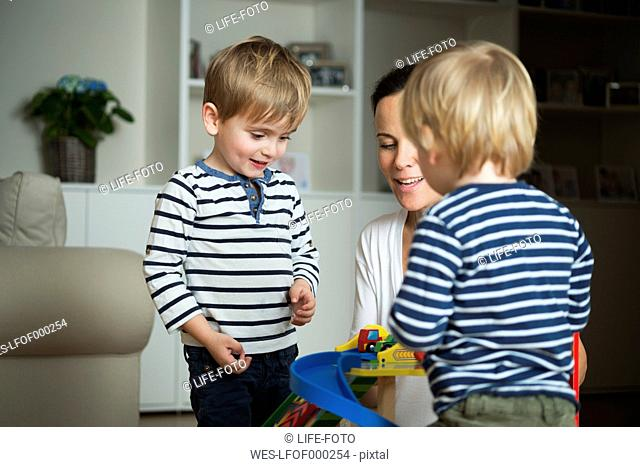 Two little boys playing at home with their mother