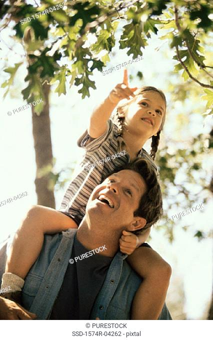 Low angle view of a girl sitting on her father's shoulders