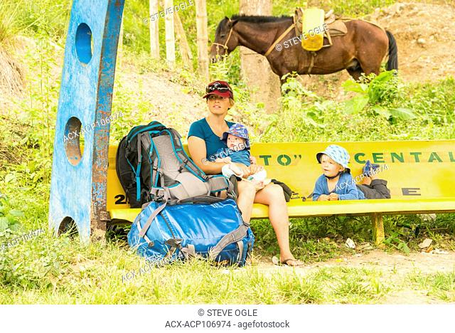 A family waits for a bus in rural