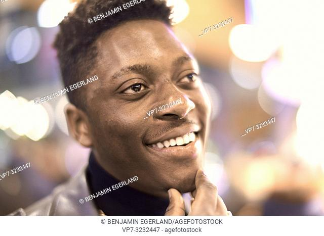 headshot of young man in city lights with positive mindset, African descent, looking aside, thinking about ideas, happy laughing, in Munich, Germany