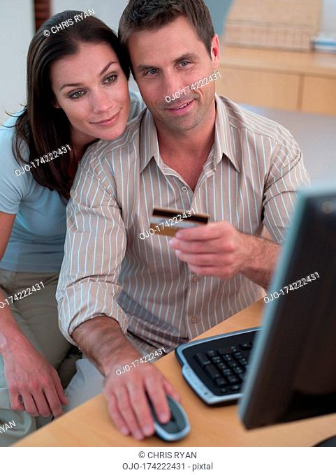 Man with credit card and computer with woman