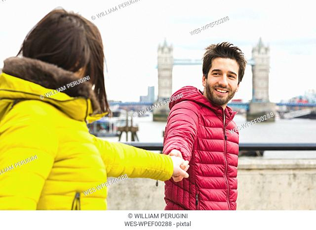 UK, London, portrait of smiling young man standing hand in hand on bridge over the Thames with his girlfriend