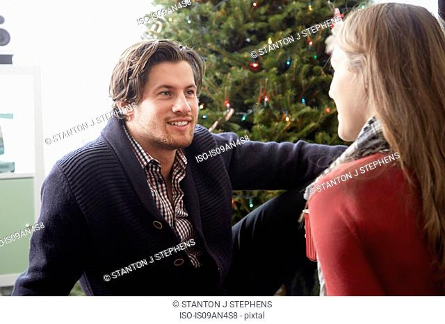 Young couple chatting in front of christmas tree