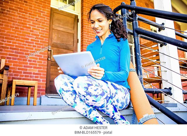 Hispanic woman using digital tablet on porch