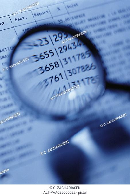Magnifying glass magnifying numbers on document, close-up, blurred