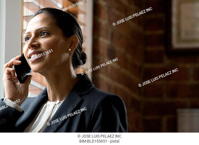Hispanic businesswoman talking on cell phone near window