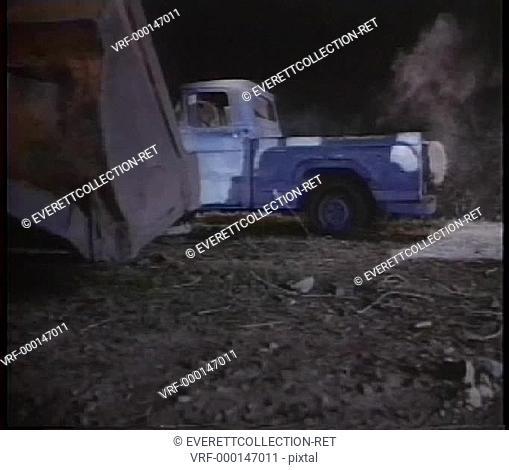 Bulldozer overturning truck down hill at night