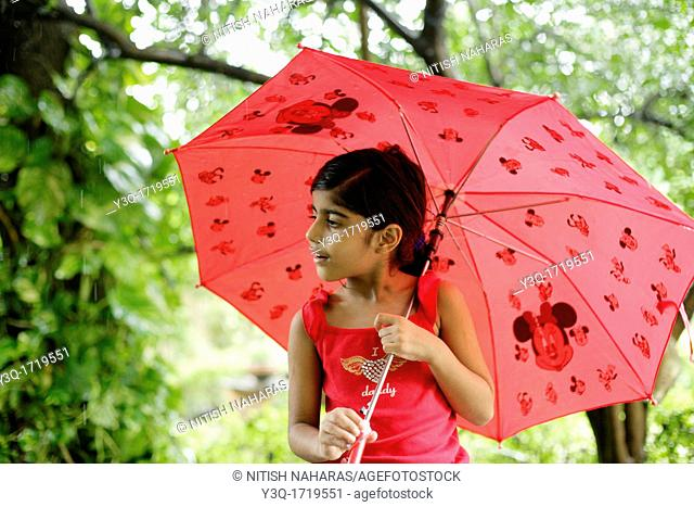 Innocent young girl holding an umbrella and enjoying the monsoon rains