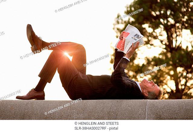 Businessman reading newspaper in park