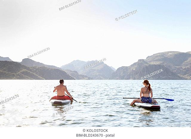 Couple sitting on paddleboards in river