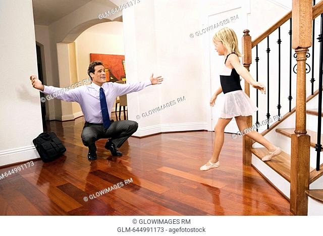 Businessman receiving a warm welcome from his daughter
