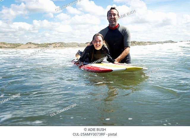 Father and daughter surfing in the sea