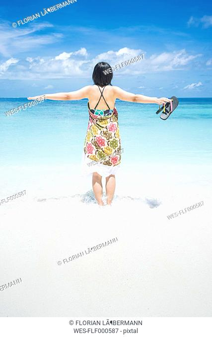 Maledives, Ari Atoll, young woman with outstretched arms standing in water at seafront