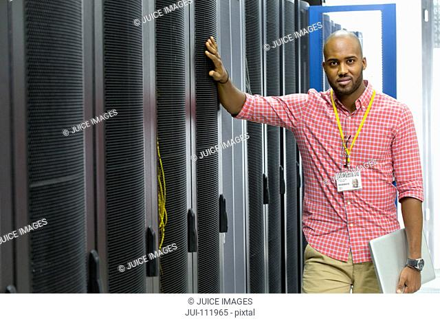 Technician looking at camera with laptop in server data centre