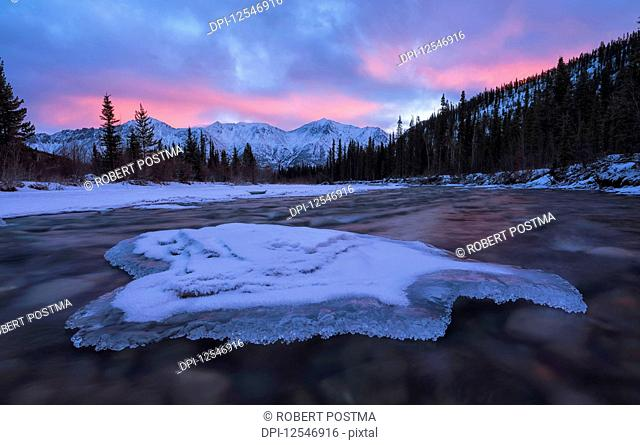 Sunrise over the mountains near Whitehorse with the Wheaton River flowing towards them and clouds reflected into the river; Whitehorse, Yukon, Canada