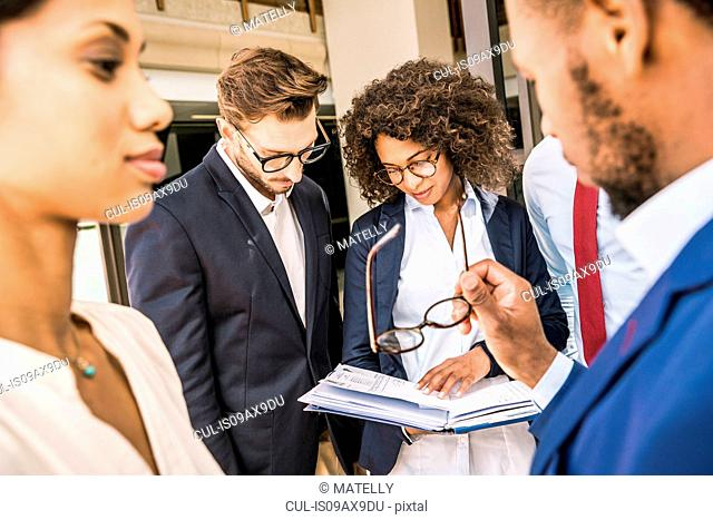 Business team preparing paperwork outside office