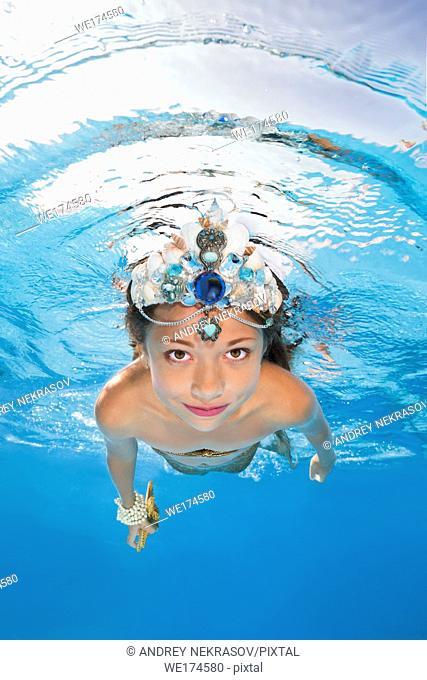 A girl in a mermaid costume poses underwater in a pool