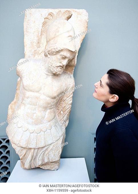 Woman looks at marble statue at The Ny Carlsberg Glyptotek art museum in Copenhagen Denmark