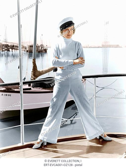 Woman in a captains hat standing on top of a sailboat Old Visuals